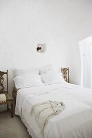 Old chairs used as bedside tables in Mediterranean bedroom