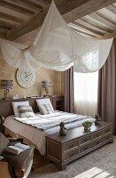 Elegantes Schlafzimmer mit aufgehängtem weissem Stoffsegel über Doppelbett an Holzbalkendecke