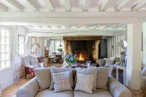 Rustic living room with wood-beamed ceiling and open fireplace