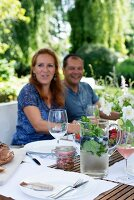 Couple seated at set garden table and glass jug of refreshing drink