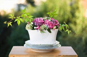 Summer bouquet in white china bowl on table outdoors