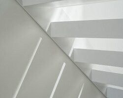 Detail of open white interior staircase with patterned of light and shade