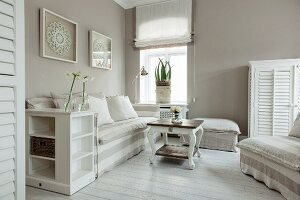Sofa and armchair with white and pale grey striped loose covers in corner of bright living room with maritime ambiance
