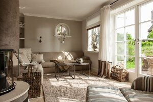 Light-flooded taupe interior with French windows, sofa and coffee table