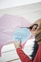 Girl cutting circles out of pastel tissue paper using template
