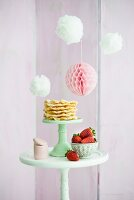Pompoms and honeycomb ball above waffles and strawberries on table