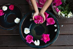 Roses floating in ceramic bowl and pink flower held in girl's hands