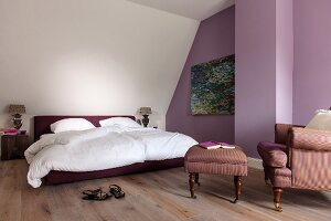 Double bed with white bed linen, comfortable armchair with matching footstool and purple-painted accent wall in attic room