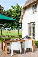 White, plastic, modern outdoor chairs and wooden table on terrace outside holiday home