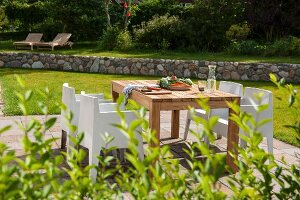 Wooden table and white, modern outdoor chairs on sunny terrace