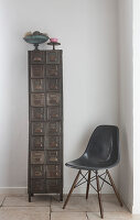 Dark grey classic shell chair next to tall, narrow, vintage metal cabinet in corner