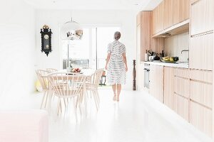 Kitchen with glossy white floor and woman walking between dining area and kitchen counter