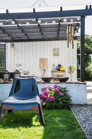 Shiny black plastic chair on lawn in front of hydrangea and pergola