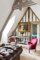 Loungebereich im Dachgeschoss mit pinkfarbenem Armlehnessel und Gemälde im Goldrahmen