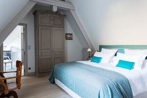 Double bed with blue checked blanket and white bed linen in attic bedroom