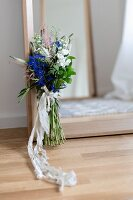 Bunch of wild flowers with lace ribbon leaning against mirror on floor