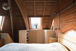 Bedroom with vaulted ceiling and modern wooden furniture in converted church