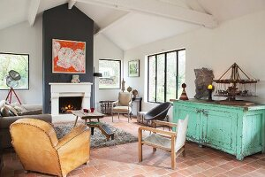 Various vintage chairs and terracotta floor in living room