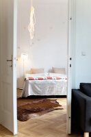 Cowhide rug and rope light in bedroom seen through open double doors