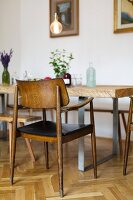 Rustic dining table and vintage chairs on herringbone parquet floor