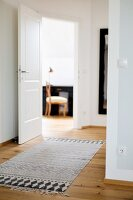 Rug with ethnic black and white print in hallway