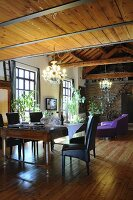 Antique dining table and black leather chairs in front of purple sofa in loft apartment
