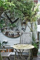 Weathered table and wooden chairs on terrace in front of vintage station clock face on climber-covered brick wall