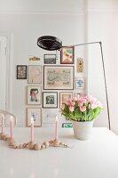 Kerzenleuchter aus Holzperlen und Tulpenstrauß vor Bildergalerie