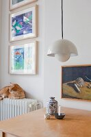 Pendant lamp above table and cat sitting on radiator