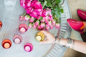 Colourful Oriental tealight holders and bunch of roses on silver tray