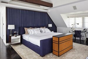 Open-plan bedroom with blue accent wall behind bed