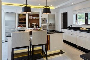 Large black and white kitchen with island counter, recessed ceiling spotlights and plinth lights