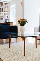 White vase of flowers on coffee table with glass top in front of dark blue armchair