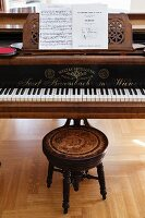 Music on stand of grand piano and antique stool with turned legs
