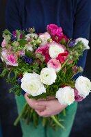 Hände halten Blumenstrauss mit Ranunkeln und Anemonen