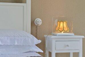 Lit, vintage bedside lamp in glass case on white bedside table with drawer