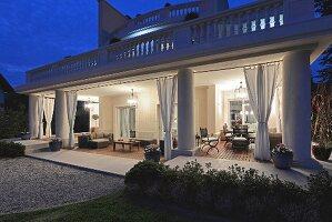 Villa at night; illuminated veranda with gathered curtains and seating