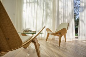 Wegner Shell Chair on oak floor in front of windows with airy curtains