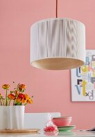 A pendent lamp with light fabric over bent wooden veneer over a table laid with buttercups against a pink wall