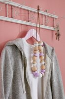 DIY-Holzkugelkette teilweise bemalt an nostalgischer Garderobenleiste aufgehängt