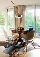 Modern shell chairs around antique table on cowhide rug