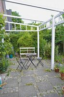 Garden chairs and a table on a terrace with a white painted pergola frame and paving slabs