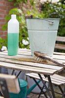 Frühjahrsputz auf der Terrasse, Vintage Metalleimer und Putzutensilien auf Gartentisch