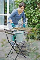 Spring cleaning on a terrace, a woman cleaning a garden table
