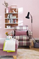 A checked upholstered armchair with a footstool against a purple wall with a wall shelf