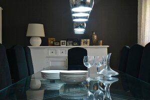 Glastisch mit Geschirr unter Pendelleuchten in dunklem Esszimmer