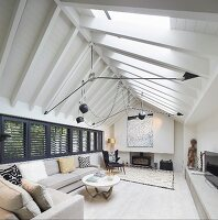 Pale sofa set in living room with exposed beams under roof ridge