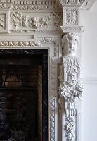 Detail of fireplace with ornate stucco elements and bust
