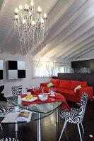 Modern, zebra-patterned chairs around glass table below chandelier in open-plan living area