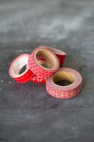 Several rolls of red, patterned washi tape on grey surface